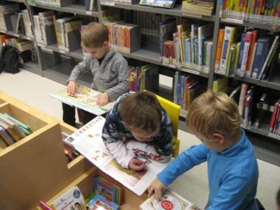 Wissbegierig werden die Bücher betrachtet. Die Kinder zeigen einander, was sie entdeckt haben.